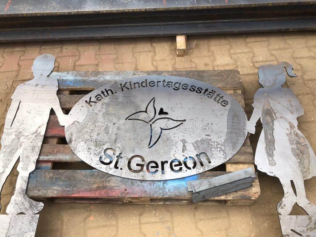Für die Kita St. Gereon haben wir in Zusammenarbeit mit dem Personal dieses Eingangsschild entworfen und gefertigt. Es ist aus Schwarzblech hergestellt und soll bald, nach dem Einbetonieren,in erwünschter Rostoptik erstrahlen.